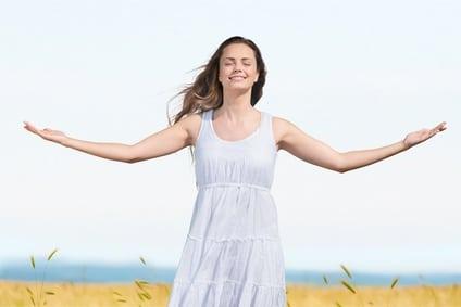 Frau im weissen Kleid mit geöffneten Armen